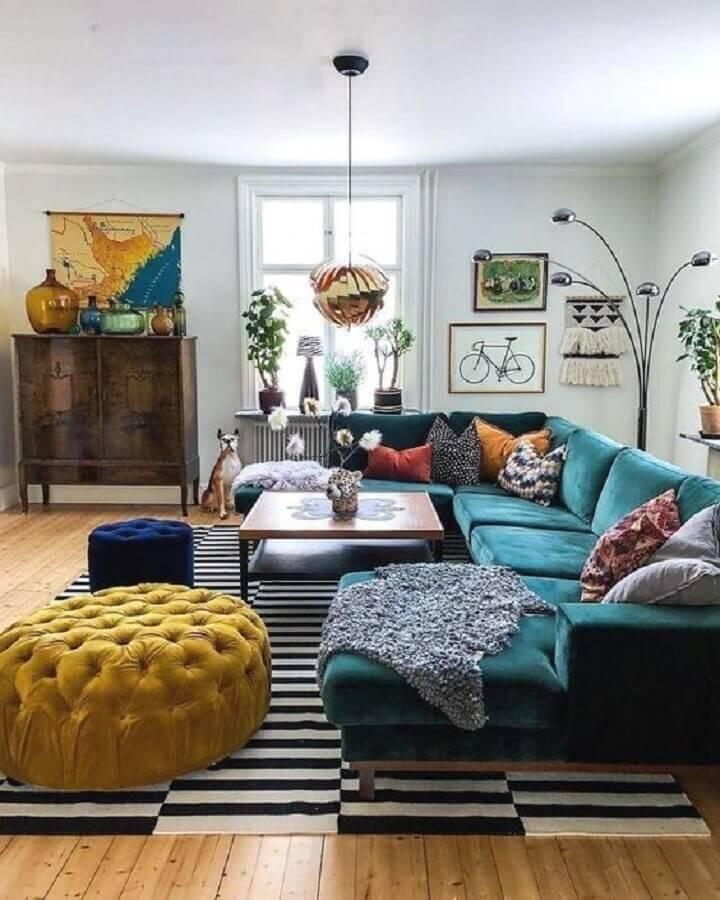 sala com sofá verde decorada com tapete preto e branco e puffs azul e amarelo Foto Ten is Extreme Shop