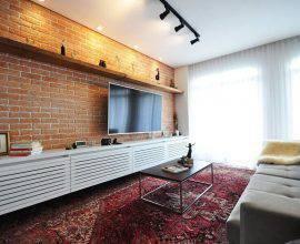 sala de estar decorada com parede de tijolinho e trilho de luz