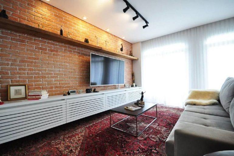 sala de estar decorada com parede de tijolo à vista e trilho de luz
