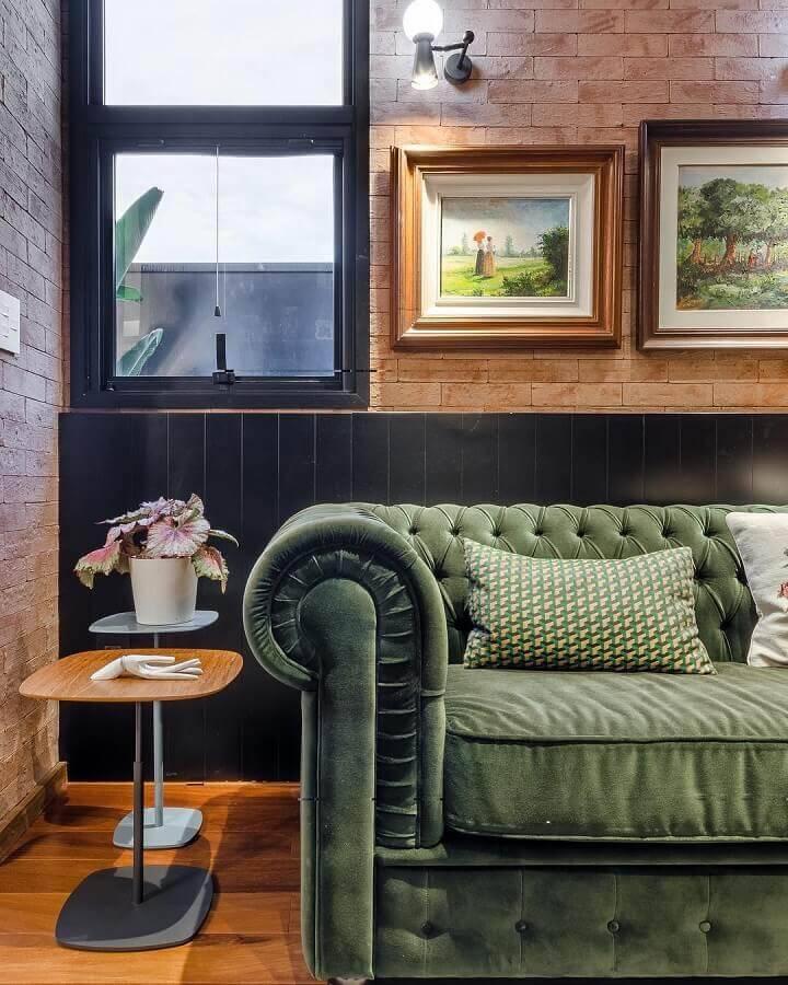 sala decorada com parede de tijolinho e sofá verde com acabamento capitonê Foto Andrea Murão