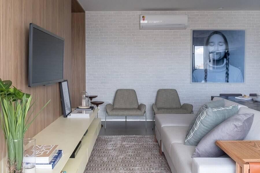 sala moderna decorada com parede de tijolinho branca e quadro grande