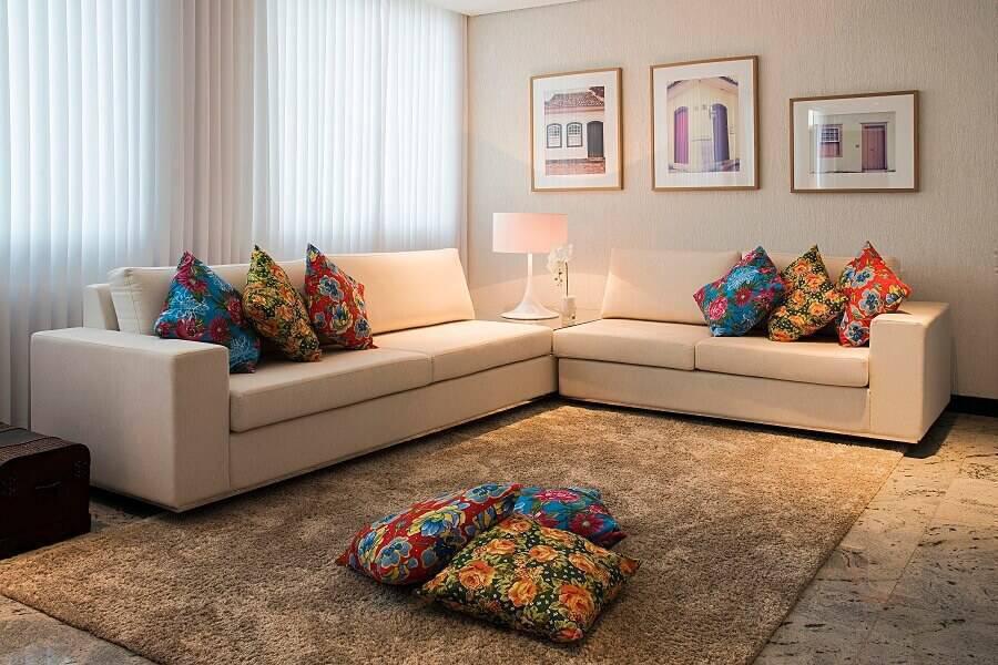 sala simples decorada com quadros e almofadas coloridas
