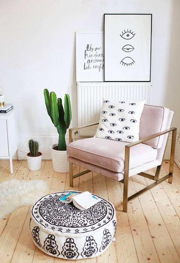 Sala de estar com poltrona rosa e vaso com diferentes tipos de cactos