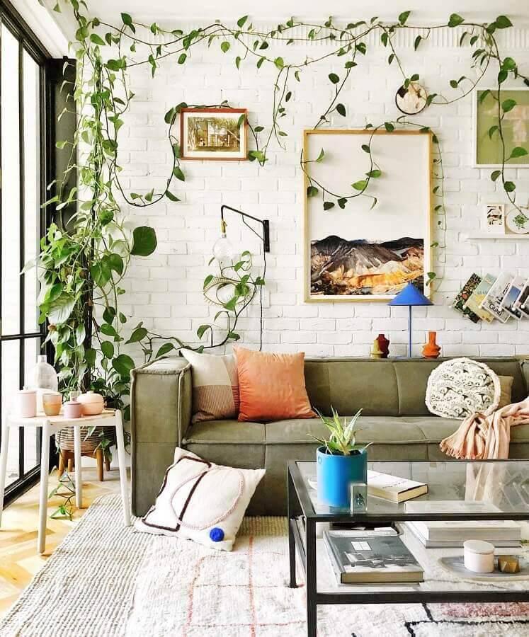 sofá verde musgo para sala decorada com parede de tijolinho e plantas Foto Jono Fleming