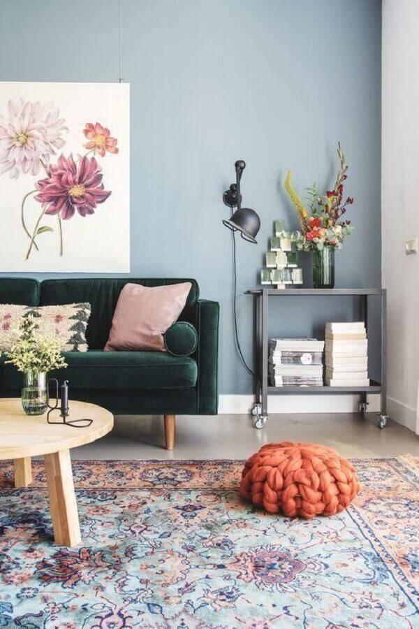 sofá verde para sala com parede azul clara e mesa de centro de madeira redonda Foto Ten is Extreme Shop