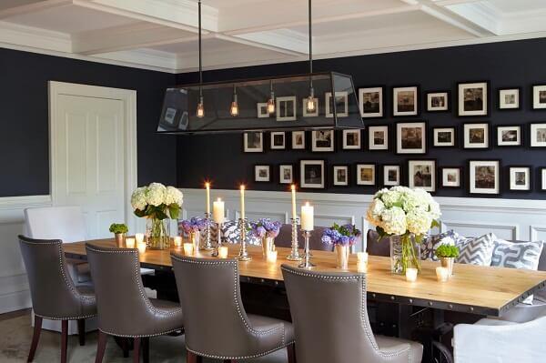 A parede preta da sala de jantar serviu de apoio diversos quadros fotográficos