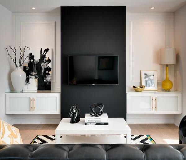 Sala de TV com parede preta e sofá de couro