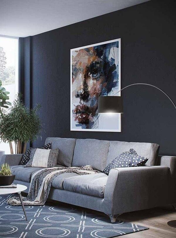 Sala de estar com parede preta e sofá cinza de três lugares