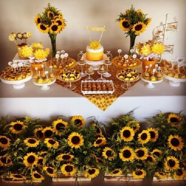 Caixotes de madeira e flores decoram a mesa do bolo da festa tema girassol
