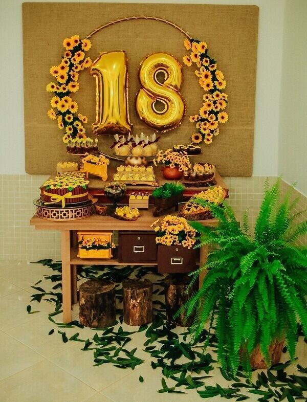 Mesa simples para festa tema girassol com mesa de madeira e flor de samambaia