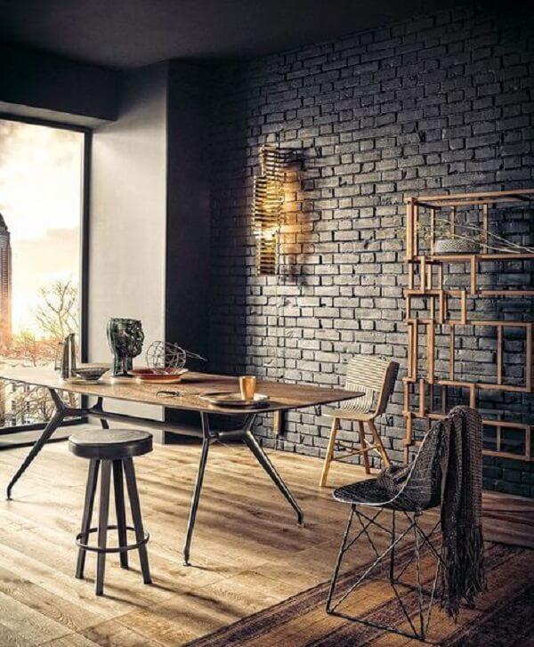 Mesa de madeira, estante de ferro e parede de tijolinho preta decoram o espaço