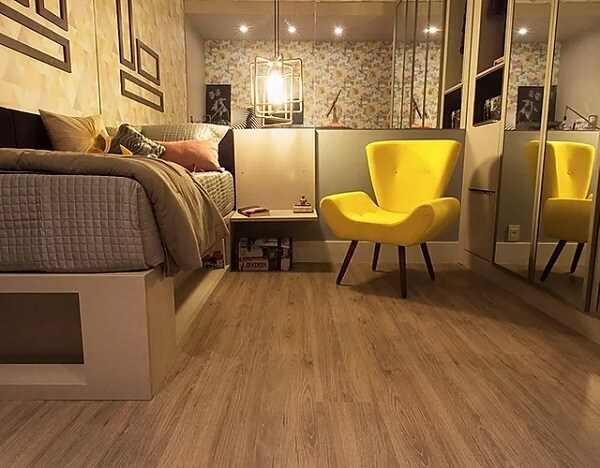 Quarto com parede espelhada e piso laminado