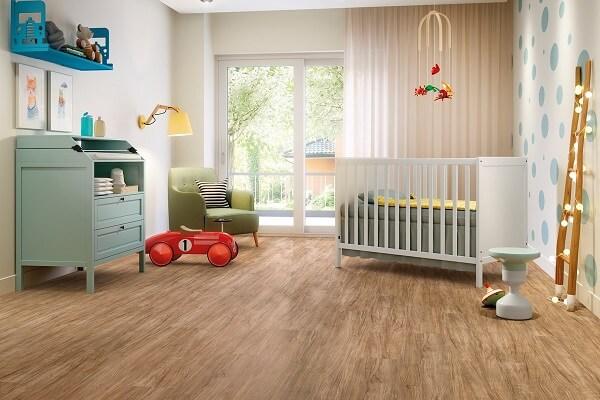 O quarto de bebê recebeu acabamento com piso laminado