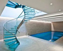 A escada de vidro nos leva até a área de lazer do imóvel