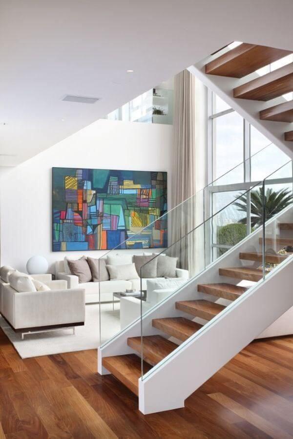 A escada de madeira com vidro se integra perfeitamente com a decoração da sala de estar