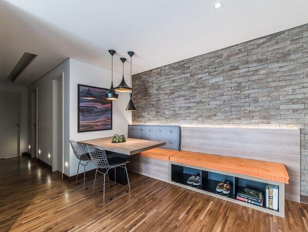 Ambiente criativo com mesa de canto de jantar, parede de tijolinho e banco estendido com nichos