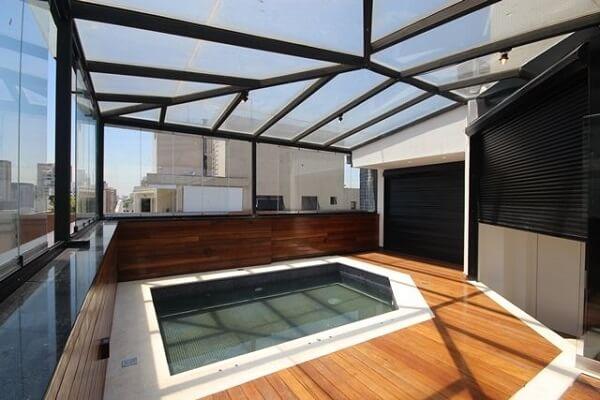 Ambiente com cobertura de vidro e deck de madeira