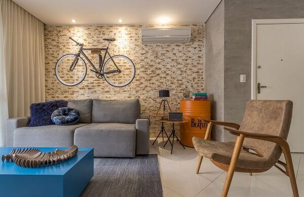 Ambiente descontraído com poltrona de veludo marrom e sofá retrátil cinza