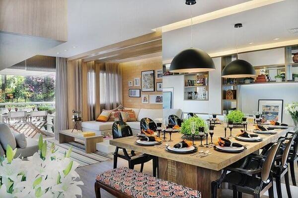Ambiente integrado com mesa de jantar de madeira e cadeiras pretas