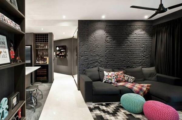 Sala de estar com parede de tijolinho preta e puffs de crochê