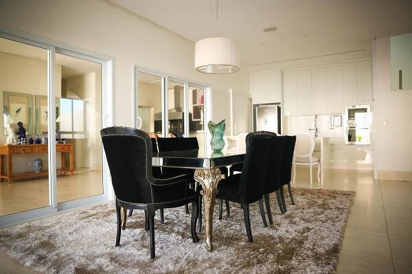 Cadeiras de veludo preto e tapete de pelinho claro