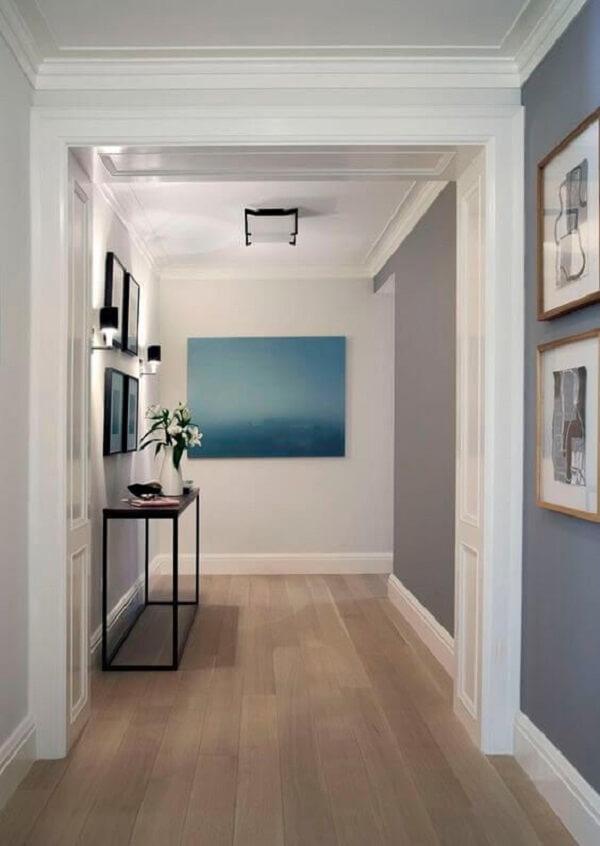 O corredor dessa casa recebeu acabamento com piso laminado claro