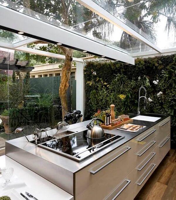 Cozinha iluminada com cobertura de vidro e jardim vertical