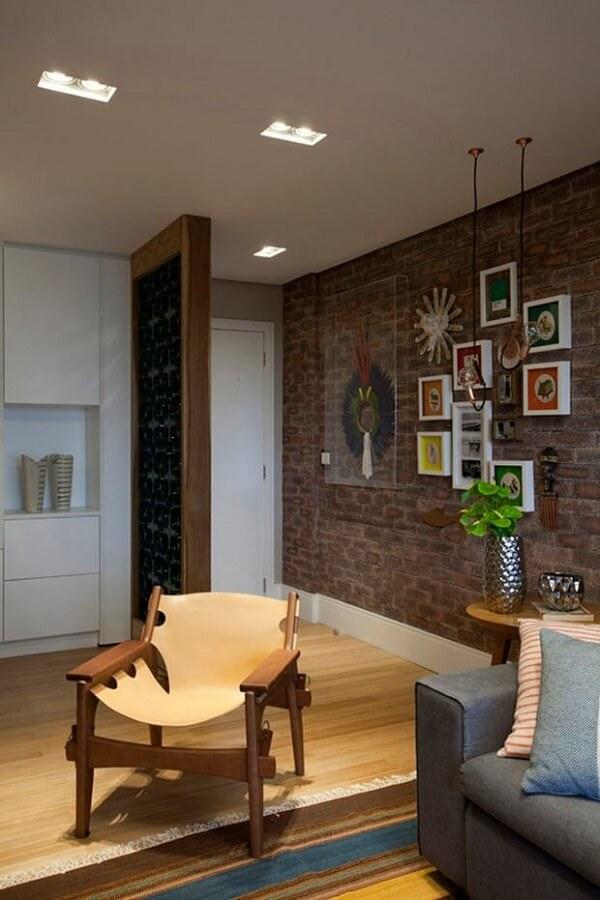 Parede de tijolinho aparente e piso laminado encantam a decoração dessa casa