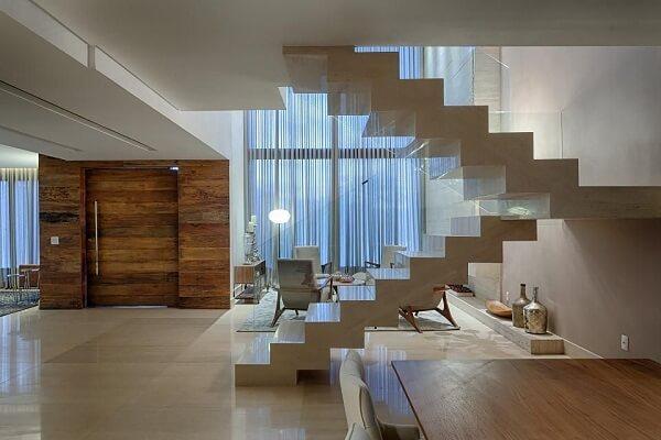 Escada em formato U com guarda corpo de vidro