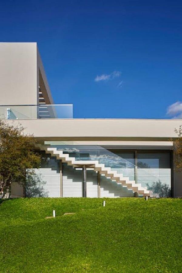 Escada externa com guarda corpo de vidro se integra ao jardim
