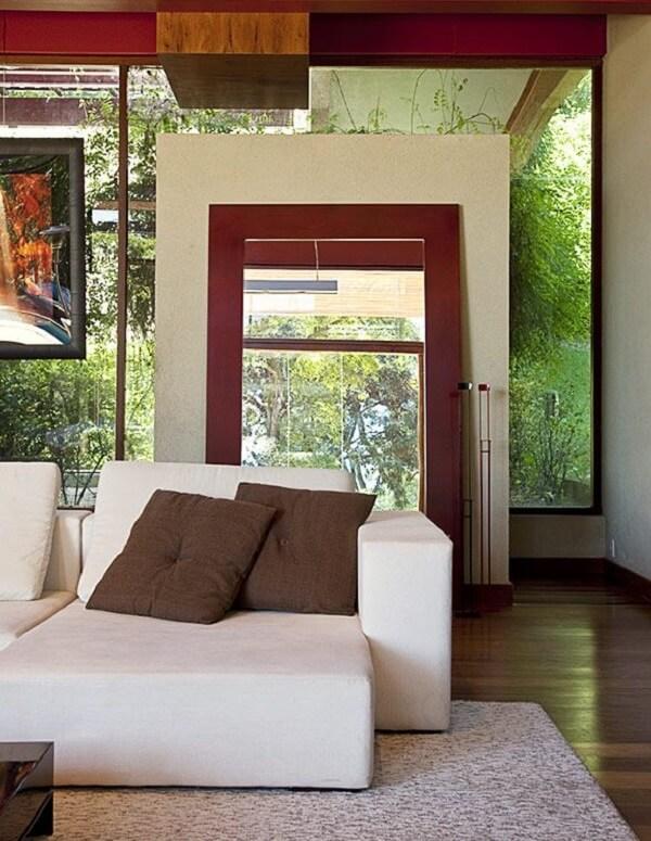 Espelho com moldura vermelha e sofá retrátil claro