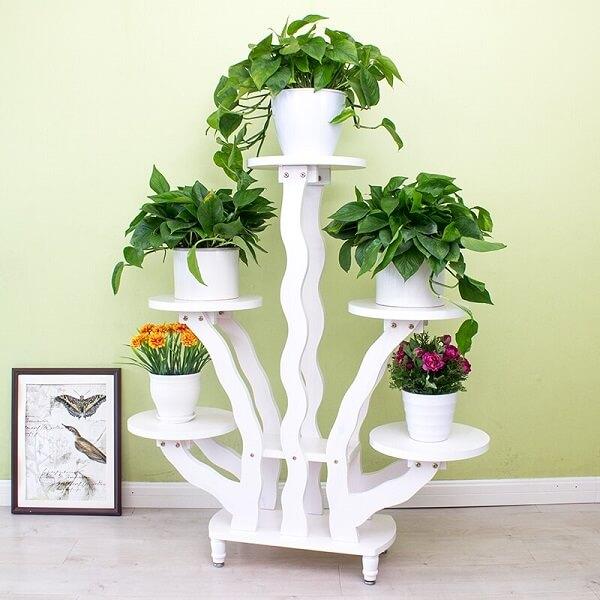 Floreira de madeira branca sustenta cinco flores em sua estrutura