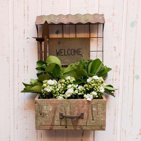 Floreira de madeira para porta de entrada recepciona os visitantes da casa