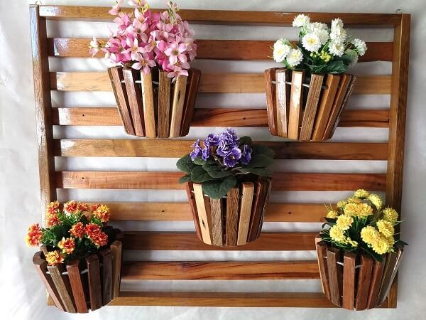 Floreira de madeira sustenta cinco vasos de flores