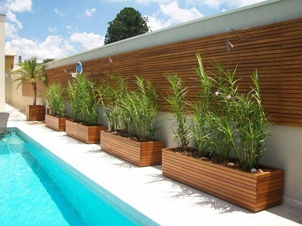 Floreira de madeira decora a borda da piscina