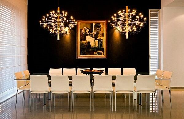 Sala de jantar ampla com parede preta e lustres dourados