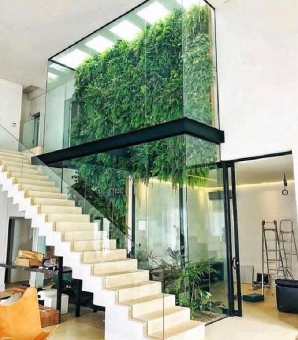 Jardim vertical fantástico e escada branca com corrimão de vidro