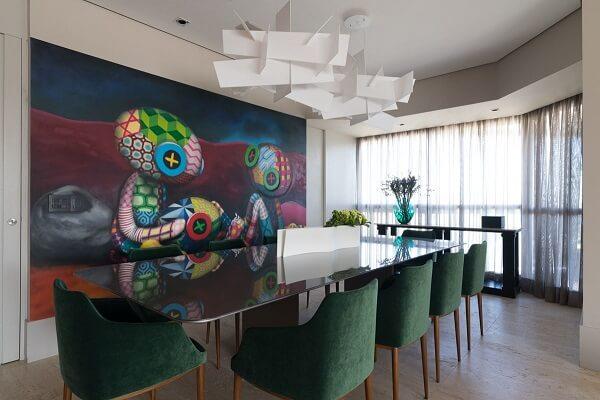 Mesa de jantar com tampo de vidro, cadeiras verdes e quadro grande colorido