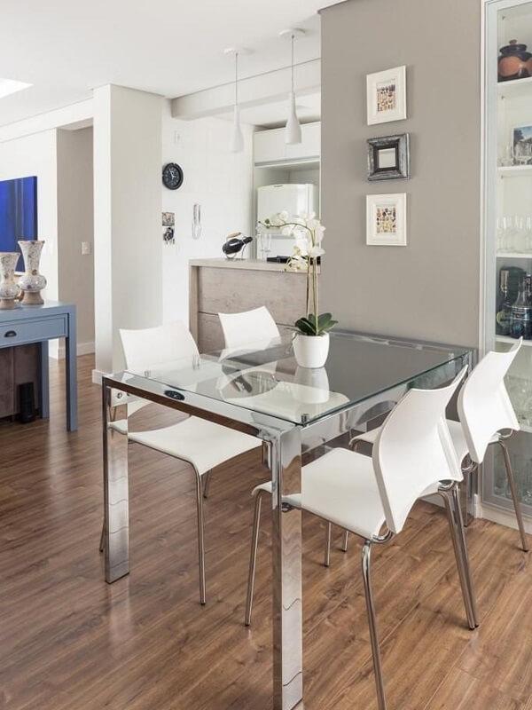Mesa de jantar com tampo de vidro e cadeiras brancas