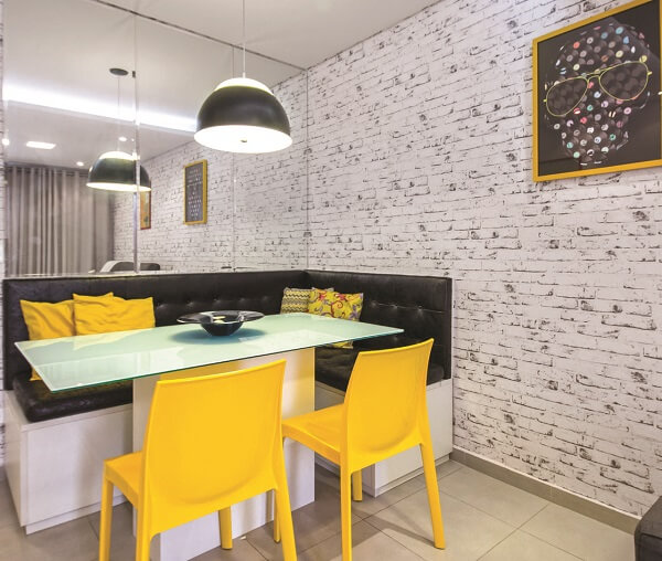 Mesa de jantar de canto, papel de parede tijolinho e cadeiras amarelas