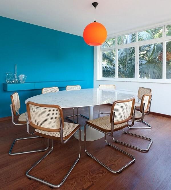 Mesa de jantar redonda com tampo de granito e pendente laranja