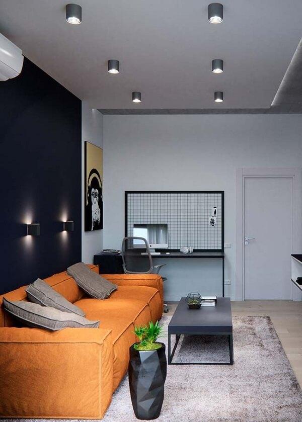 Nessa sala de estar a parede preta foi contrastada com o sofá laranja de três lugares