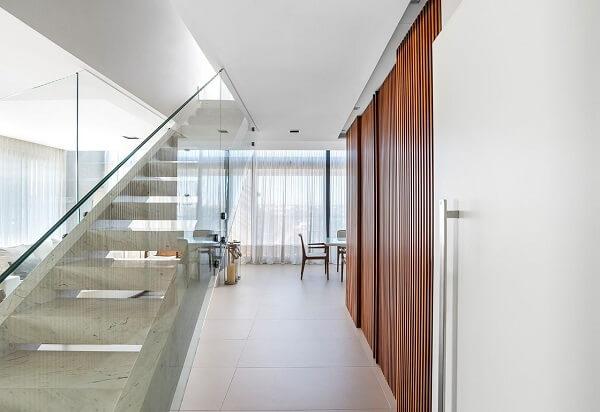 Porta de correr ripada e escada reta com guarda corpo de vidro