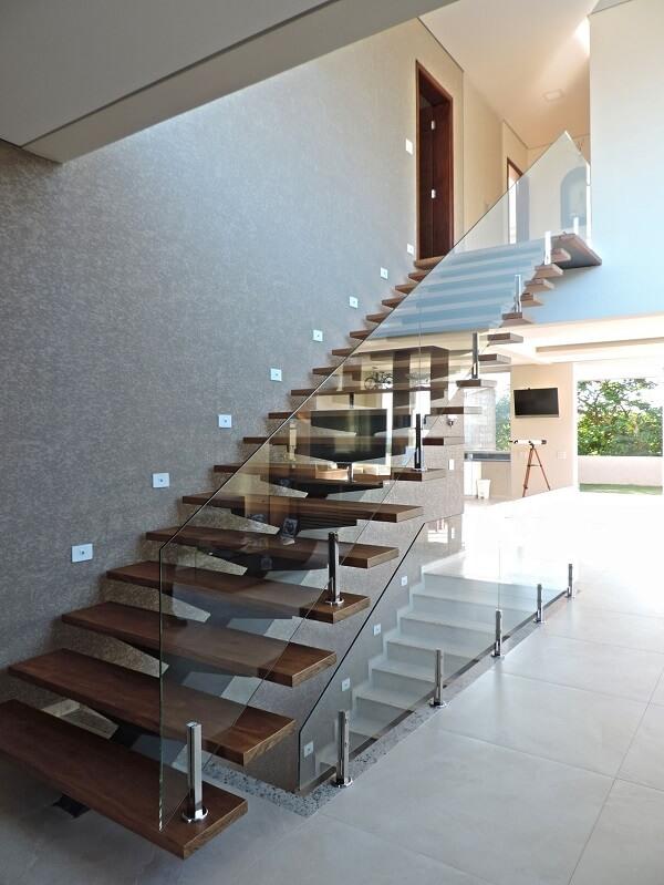 Papel de parede neutro e escada de madeira com vidro decoram o ambiente.