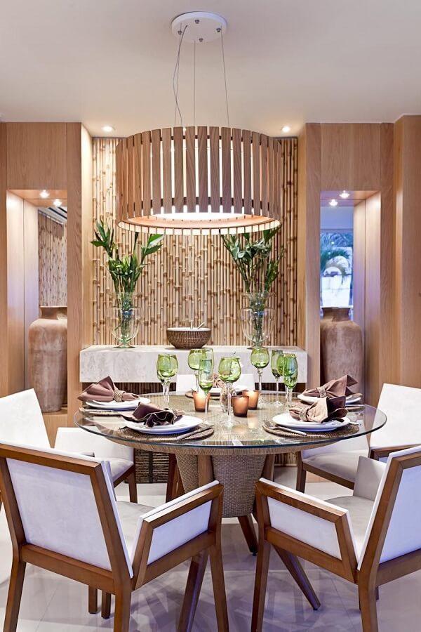 Parede com bambu natural, mesa de jantar redonda e cadeiras de couro claro