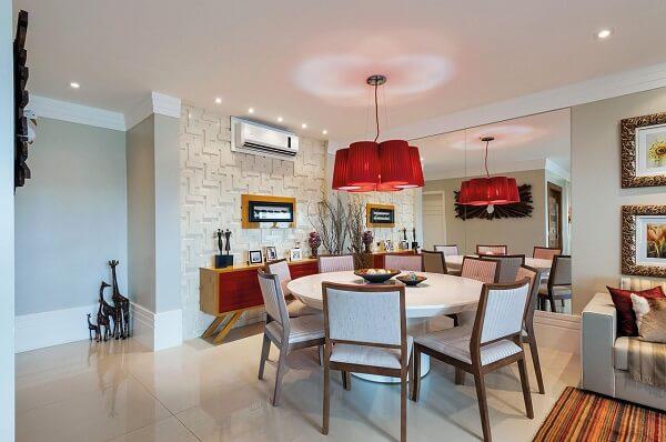 Parede com revestimento 3D, pendentes vermelhos e mesa de jantar redonda