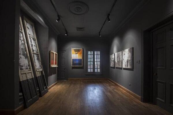 Espaço com parede preta e quadros abstratos