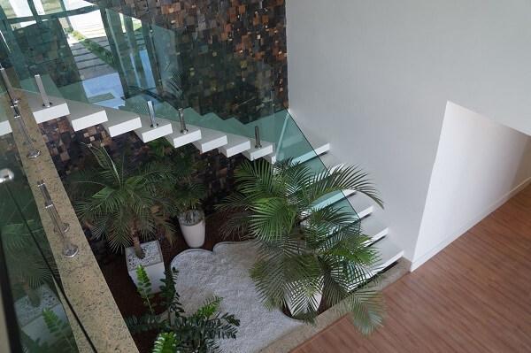 Piso de madeira, escada branca e guarda corpo de vidro se harmonizam com o jardim de inverno