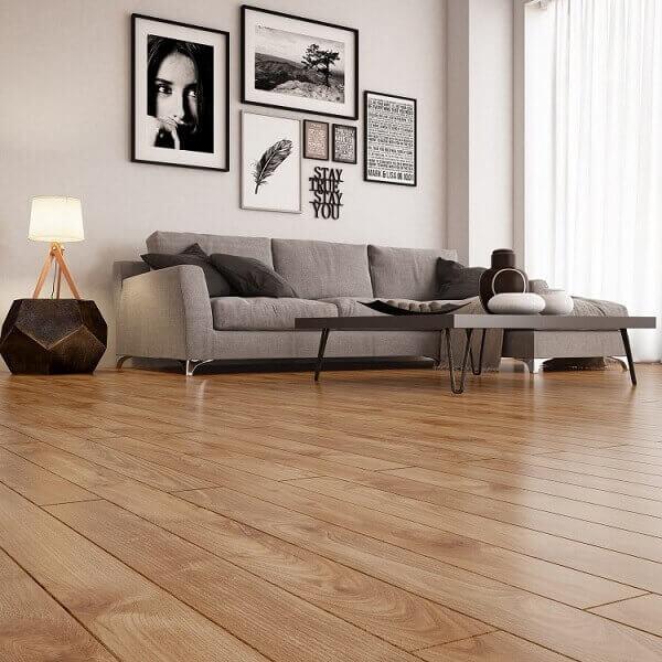 Sala de estar com piso laminado e sofá cinza 3 lugares