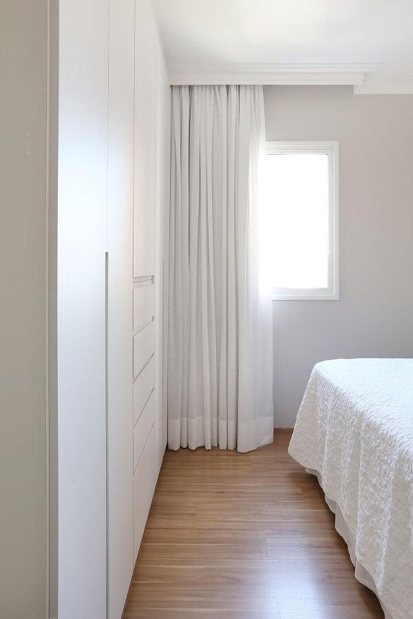 Quarto de casal com decoração clean conta com guarda roupa branco e piso laminado
